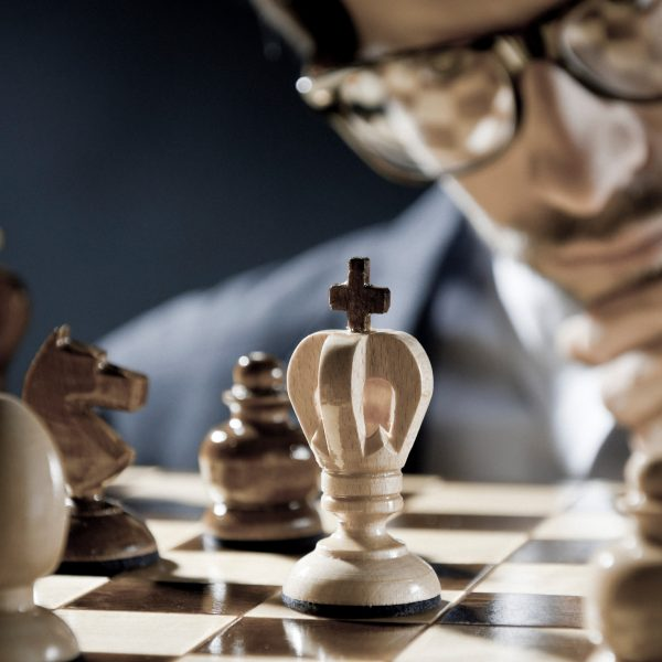 Man contemplating chess board.